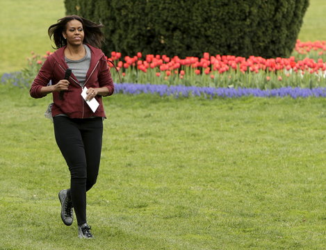United States first lady Michelle Obama runs to plans vegetables with school children during spring planting of White House vegetable garden in Washington