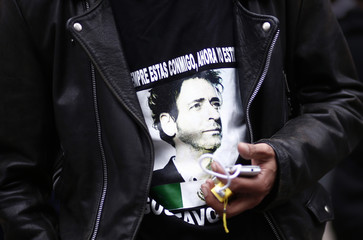 A fan wears a t-shirt with a picture of Argentine musician Cerati outside the clinic where Cerati died today at the age of 55 in Buenos Aires