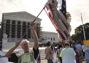 A man waves a self-made U.S. flag covered in fake currency and corporate logos during a protest in front of the U.S. Supreme Court in Washington