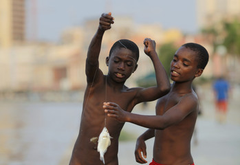 Angolan youths catch fish in the bay of the capital Luanda