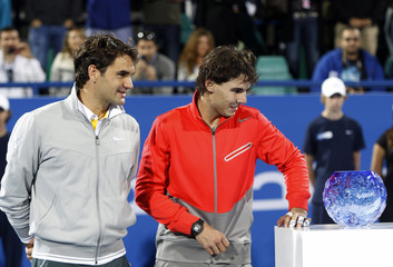 Nadal of Spain and Federer of Switzerland look at one of the trophies after their final match during Mubadala World Tennis Championship in Abu Dhabi