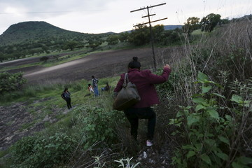 A Guatemalan woman and other immigrants head to a safe place to spend the night and protect themselves from organized crime bands in Huehuetoca, near of Mexico City