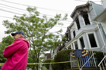 A neighbor stands on the street in front of townhouses involved in a large fire the night before, in the Staten Island borough of New York