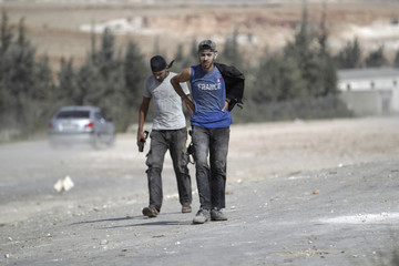 Rebel fighters covered with dust walk near a site hit by what activists said were airstrikes carried out by the Russian air force in the town of Babila, in the southern countryside of Idlib