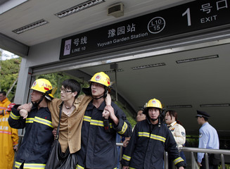 Firemen helps evacuate a victim outside  the Yuyuan Garden station after a subway crash in Shanghai