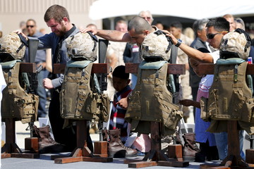 Fellow marines pay their respects to members of the 3rd Marine Aircraft Wing during a memorial service at Camp Pendleton