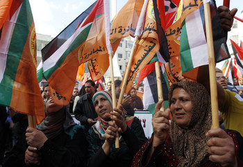 Palestinian protesters wave Palestinian and Popular Front for the Liberation of Palestine flags during a demonstration in Ramallah