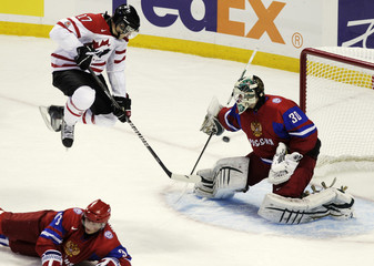Canada's Foligno jumps over Russia's Pivtsakin as Russia's goaltender Bobkov looks for the shot during the IIHF World Junior Championships in Buffalo
