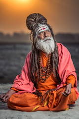 Portrait of sadhu sitting with sunrise behind him, Varanasi, India.