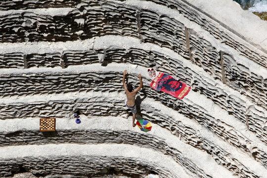 "Man climbs a rock next to a towel depicting revolutionary leader Ernesto ""Che"" Guevara, on a beach in Naqoura, southern Lebanon"