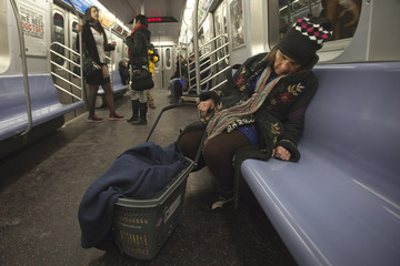 """A woman sleeps as people take part in the """"No Pants Subway Ride"""" in New York"""