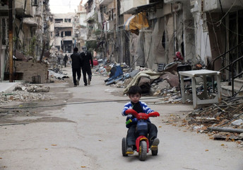 A child rides a bicycle near damaged buildings in the besieged area of Homs
