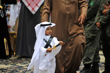"A Saudi prince holds a sword to participate in a traditional Saudi dance known as ""Arda"" during the Janadriya culture festival at Der'iya in Riyadh"
