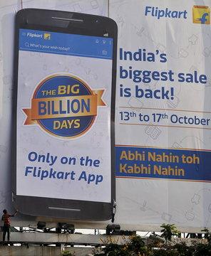 Worker removes an advertisement billboard of Indian online marketplace Flipkart, installed along the roadside in Mumbai, India