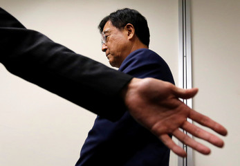 Mitsubishi Motors Corp's Chairman and Chief Executive Officer Masuko reacts after submitting a report to Land, Infrastructure, Transport and Tourism Ministry's Road Transport Bureau Director-General Fujii at the ministry in Tokyo