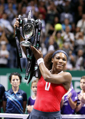 Serena Williams of the U.S. celebrates with the trophy after her victory against Russia's Sharapova after their final WTA tennis championships match in Istanbul
