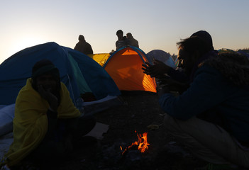 Migrants gather round a fire in makeshift camp at collection point in Roszke