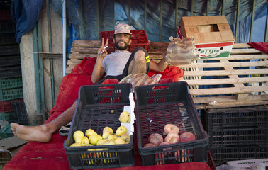 A fruit seller poses for a picture while waiting to sell the last of his stock at a fruit and vegetable market in Tripoli