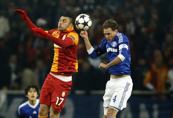 Schalke 04's Hoewedes and Galatasaray's Yilmaz head a ball during the Champions League soccer match in Gelsenkirchen