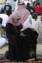 A girl adjusts her sister's head scarf during prayers for Eid al-Adha in Riyadh