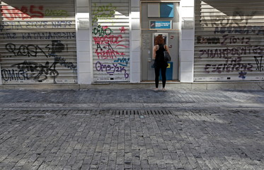 A woman withdraws money at an ATM outside a National Bank branch in Athens