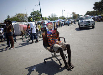 A boy holds a picture of former president Jean-Bertrand Aristide as he sits on a chair outside the presidential palace during a visit by France's President Nicolas Sarkozy to Port-au-Prince, Haiti