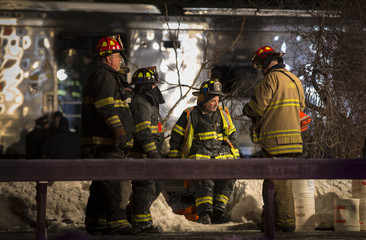 Firefighters and Emergency workers stand near a burnt Metropolitan Transportation Authority Metro North Railroad commuter train car near the town of Valhalla