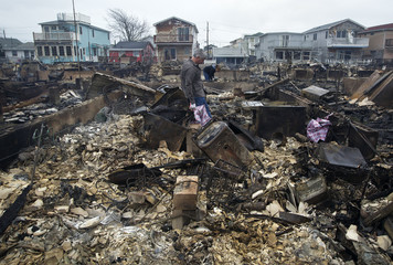 Tom and Deidre Duffy look through the wreckage of their home devastated by fire and the effects of Hurricane Sandy are seen the Breezy Point section of the Queens borough of New York
