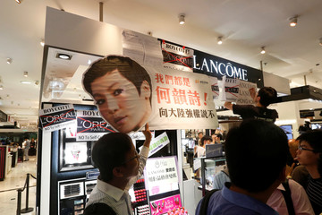 Protesters demonstrate in front of a stall of the luxury skincare brand Lancome inside a shopping mall in Hong Kong