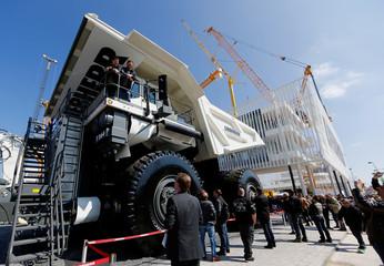 Visitors look at a giant dump truck at the 'Bauma' Trade Fair in Munich