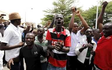 People cheer and dance outside the Radio Publique Africaine (RPA) broadcasting studio during protests in Burundi's capital Bujumbura