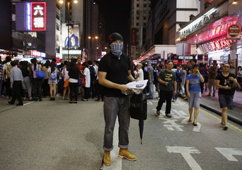 John, who works in design, poses at Mongkok shopping district in Hong Kong