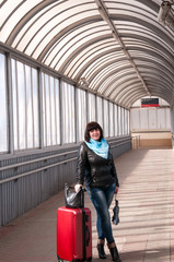 Girl with a suitcase is walking along train station