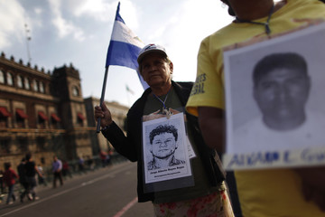 A woman from the Caravan of Central American Mothers holds up a Nicaraguan flag and a photo of a missing migrant during a march at Zocalo Square in Mexico City