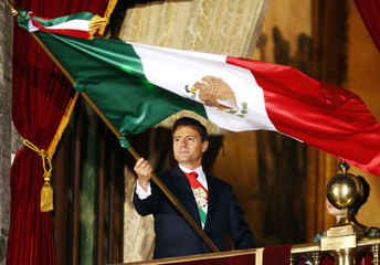 """Mexico's President Enrique Pena Nieto waves the national flag after he shouted the """"Cry of Independence"""" as Mexico marks the 203rd anniversary of the day rebel priest Manuel Hidalgo set it on the path to independence in Mexico City"""