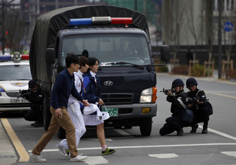 Pedestrians walk on a crosswalk as South Korean police officers take part in an anti-terror and security drill at the Integrated Government Complex in Sejong