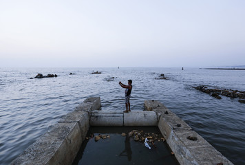 A man uses a mobile phone to take a photo of the sunset while standing on an under construction jetty in Mumbai