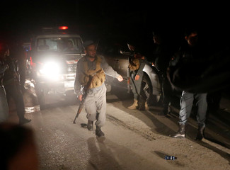 Afghan policemen stand guard at the site of an attack at American University of Afghanistan in Kabul