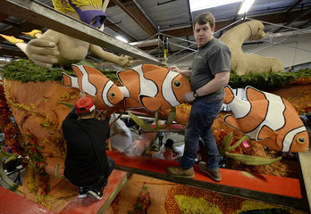 A float supervisor looks on as a man places a clown fish figure on SeaWorld's Tournament of Roses Parade float at Fiesta Parade Floats in Irwindale