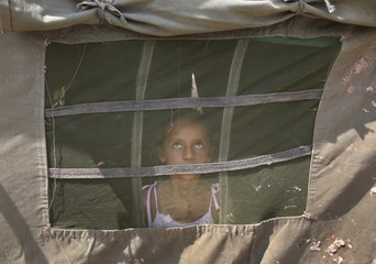 A girl from a flood-affected area watches a military chopper from inside an Indian Army tent at a relief camp on the outskirts of Jammu