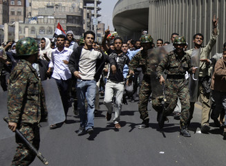 Anti-government protesters overpower riot policemen after they tried to prevent them from marching to the presidential palace in Sanaa