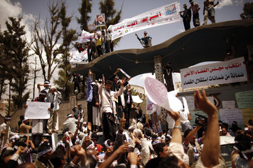 Members of the Peaceful Revolution Salvation Front shout slogans as they gather outside the Ministry of Justice during a demonstration in Sanaa