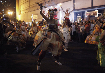 """Afro-Brazilian women dance on the street during the annual block party known as the """"Afro Ilu Oba De Min"""" in Sao Paulo"""