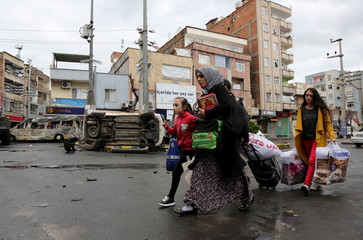 Residents carry their belongings as they flee from Baglar district, which is partially under curfew, in the Kurdish-dominated southeastern city of Diyarbakir