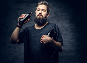 Portrait of bearded hipster male drinks beer.