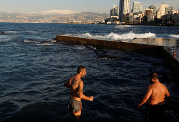 Two men swim in the Mediterranean sea on a cold day at the private beach of the American University of Beirut, with snow-covered Mount Sannine seen in the background in Beirut