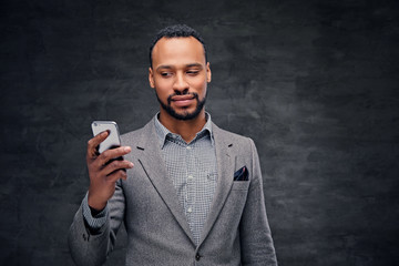 Portrait of elegant bearded black  male in a suit holds smart phone.