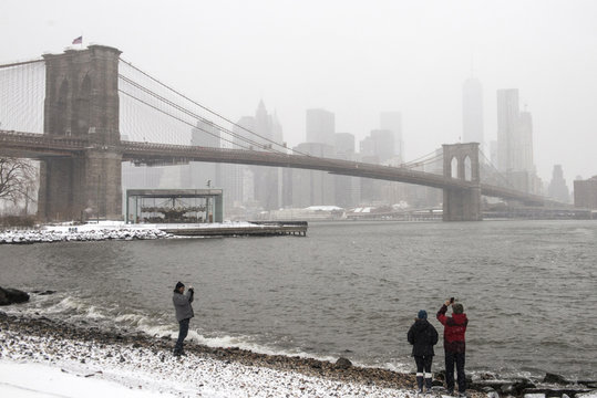 The Manhattan skyline and the Brooklyn Bridge is seen in the background as bystanders take photos after a snow storm in New York