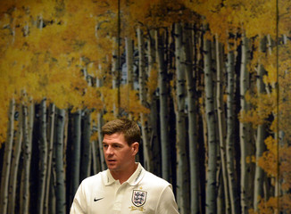 England's Steven Gerrard walks past a photo backdrop of an autumn scene as he arrives for a news conference, ahead of their 2014 World Cup qualifying soccer match against Montenegro, at the team hotel near London