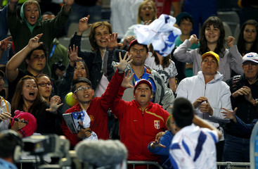 Djokovic of Serbia throws his towel to the crowd after winning his match against Dodig of Croatia at the Australian Open tennis tournament in Melbourne